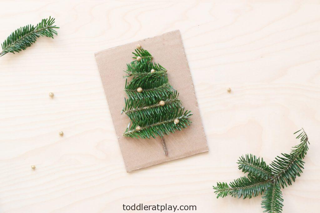 If you're looking for an easy, low-prep Christmas craft, then look no further! This Recycled Christmas Tree Craftonly requires a piece of cardboard, liquid school glue, Christmas tree branches and glittery foam balls.